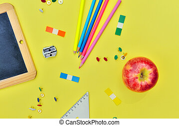 top view on suplies of school and red apple on yellow background
