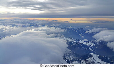 Top view on the Alps, covered with snow and clouds