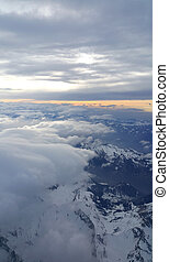 Top view on the Alps covered with snow and clouds