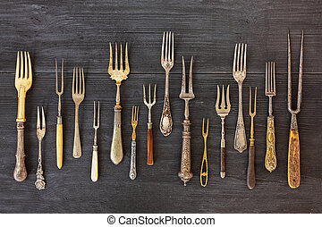 Top view on various forks, old utensils. Flat lay on rustic wooden background. Antique kitchenware background