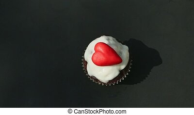 top view on white glazed chocolate cupcake decorated with red heart shaped marzipan candy served on black table surface