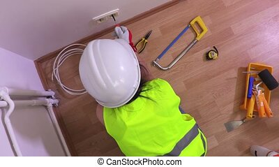 Top view on Woman electric with screwdriver near wall