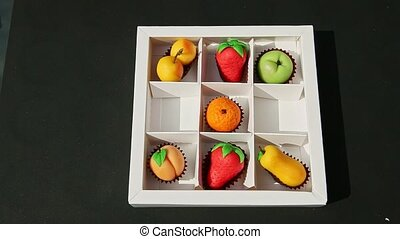 top view on woman hand puts fruits shaped marzipan candies into white gift box