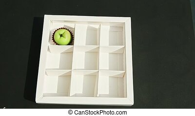 top view on woman hand puts fruits shaped marzipan candy into white gift box