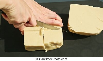 top view woman hand slice by knife big cubes of white homemade marzipan mass served on black table surface