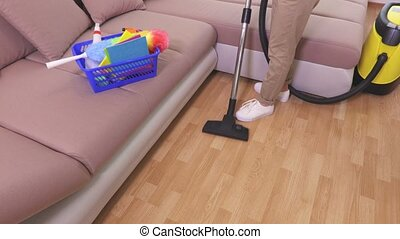 Top view on woman who clean floor with vacuum cleaner