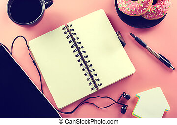 Open notebook and cup of coffee with donut on a pink background. Tinted picture.