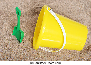 pail and shovel in the sand - top view pail and shovel in...