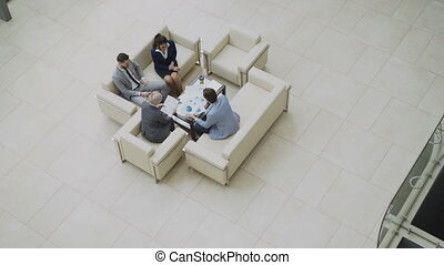 Top view pan shot of group of business people colleagues discussing financial charts sitting on couchs in lobby at modern business center