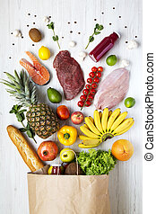 Top view, paper bag of health food on a white wooden background. From above, flat lay. Healthy eating concept.
