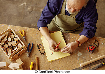 top view photo of carpenter in old age holding little cross ...