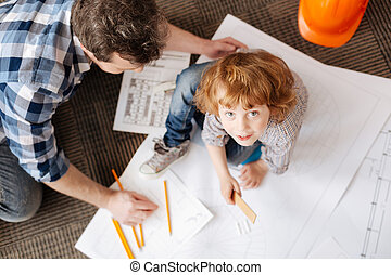 Top view photo of father and son while drawing charts