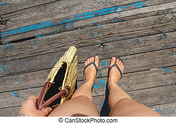 Top view, photo of legs in beach flip-flops and with a straw bag in hand on a wooden old floor. Photos on vacation, beach, summer