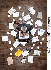 Top view photo of senior businessman on wooden floor
