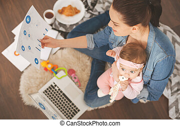 Freelance worker. Attentive female holding her baby sitting on the floor near computer while looking at diagram