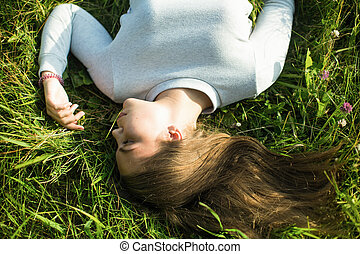 Top view picture of a young girl lying in the green grass.