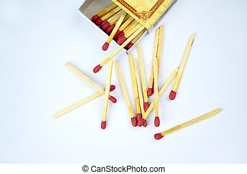Top view picture of some flammable red fire matches scattered beside a small match box