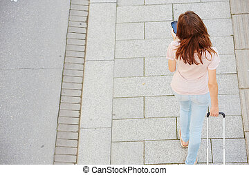 Top view portrait of female traveler with bag walking on the street