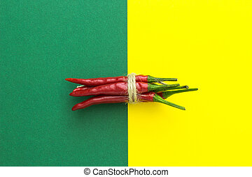 top view, red chili pepper, tied with braid on a yellow-green background, horizontally located