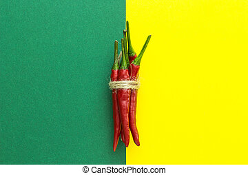 top view, red chili pepper, tied with braid on a yellow-green background, vertically arranged