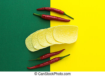 top view, red chili peppers and chips on a yellow-green background