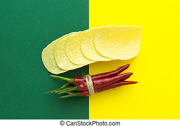 top view, red chilli, tied with braid and chips on a yellow-green background