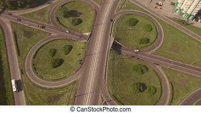 Top view round road junction in the smoll city in summer. active city traffic cars. Aerial flight. 4K