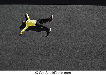 Top view runner in yellow sportswear resting lying on a ...