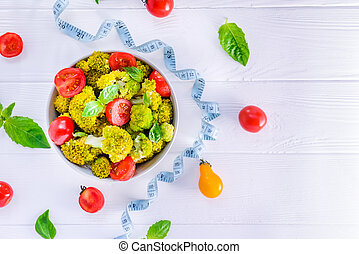 Top view Salad Bowl with cherry tomatoes, broccoli, fresh ingredients, measuring tape on the white wooden background. Healthy lifestyle concept. Detox, diet, vegitarian. Selective focus. Text space.