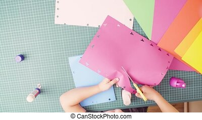Hands of little girl cutting colored paper with scissors -...
