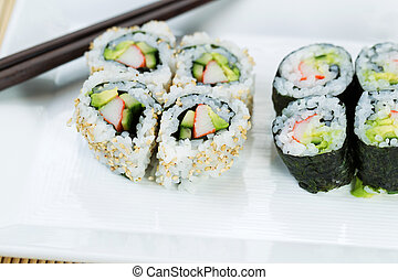Top view shot of California Rolls in white plate