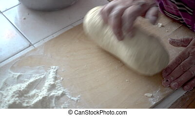 Top view shot of female hands mixing dough. Female hands knead dough on wooden board.