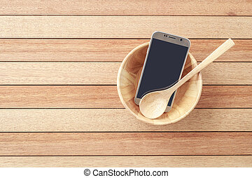 Top view smartphone in wooden bowl on wooden plank background