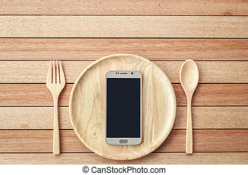 Top view smartphone on wooden dish on wooden plank background