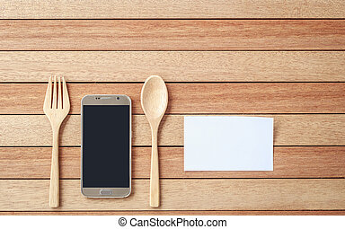 Top view smartphone, spoon and fork on wooden plank background