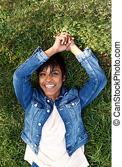 Top view smiling young african woman lying outdoors on grass