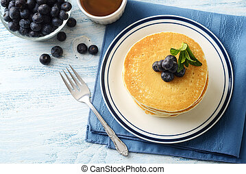 top view stack of pancakes with blueberries and bowl maple syrup