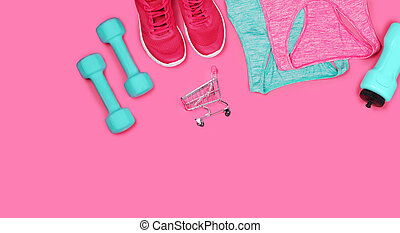 Top view still life of sneakers, dumbbells, water bottle and sportive tops on pink background