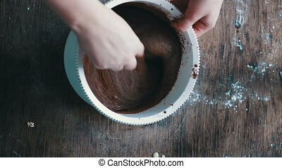 Top view stirring chocolate cookie dough with a spoon in a white plastic bowl