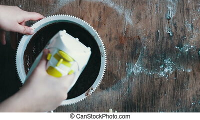 Top view of a female hand with electric mixer stirs the chocolate dough in white plastic bowl