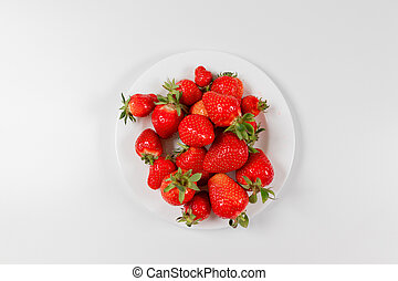 Top view strawberry in a white plate on a pink background.