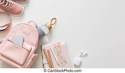 Top view stylish female backpack full of stationery supplies isolated. Back to school concept
