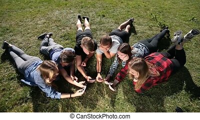 Top view teenagers in circle using phones in park