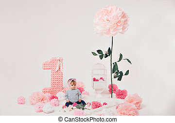 top view: the girl child mother sitting on the floor among the numbers 1, artificial flowers and a bird cage