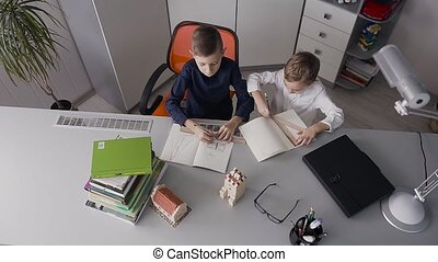 Top view. The two brothers sit at the desk at home in white room and draw drawings. The children finished doing homework and fun slapped each other in the palm of their hands