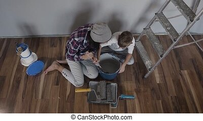 Top view. The woman and her son sit on the floor near the wall next to the ladder and mix the paint with mixer in a bucket. Repair in the apartment