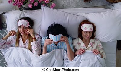 Top view, three beautiful girls go to bed and put on eye bandages to sleep after hen night and a great party.