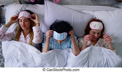 Top view, three beautiful girls go to sleep on the bed and put eye bandages to sleep.