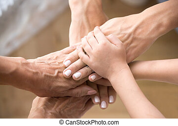 Top view three generations joining hands, showing unity and support