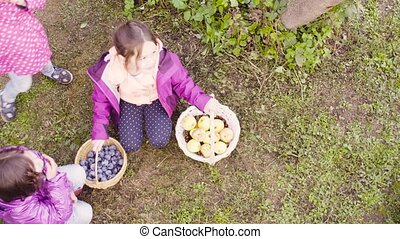Three girls sitting on the grass. One holding baskets with...